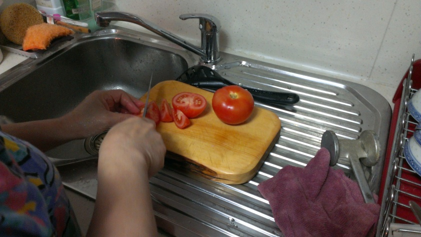 Slice up the tomatoes for the pot.
